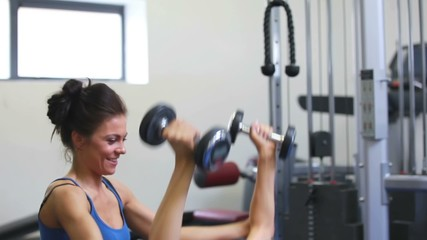 Female trainer helping woman lift weights