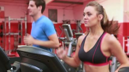 Woman and man jogging on treadmills