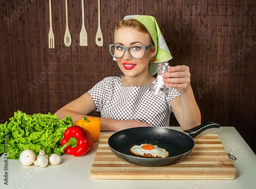 Happy funny woman cook holding salt over pan with fried egg
