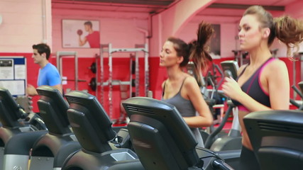 Three persons running on a treadmill