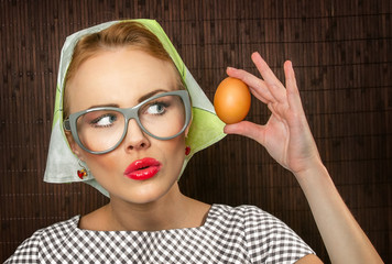 Funny woman cook holding egg,close-up