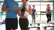 Women doing aerobics while trainer talking with woman
