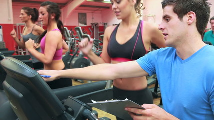 Trainer talking to woman on treadmill