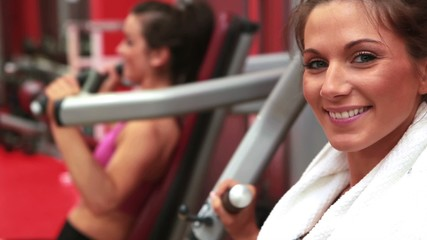 Woman using weights machine and smiling