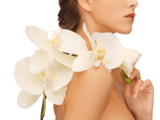 woman's shoulder and hands holding orchid flower