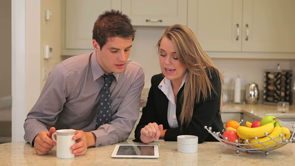 Couple sitting in the kitchen with tablet pc