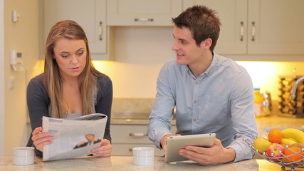 Woman reading newspaper with man holding a tablet PC