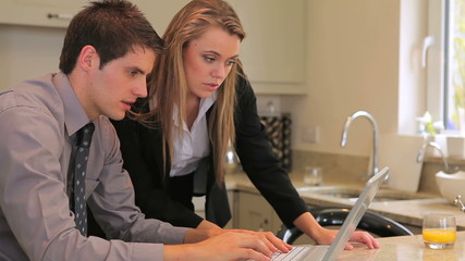 Couple sitting in the kitchen looking at laptop