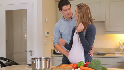 Pregnant wife cutting vegeatables and eating them with husband