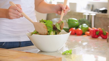 Woman is mixing salad