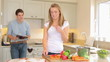 Woman chopping vegetables then feeding husband jokingly