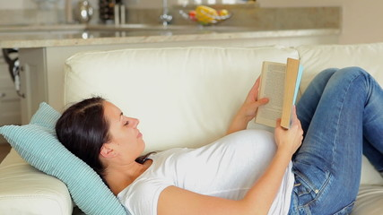 Pregnant woman reading a book on the sofa