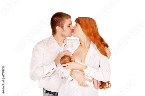 Parents kissing, baby breastfeeding