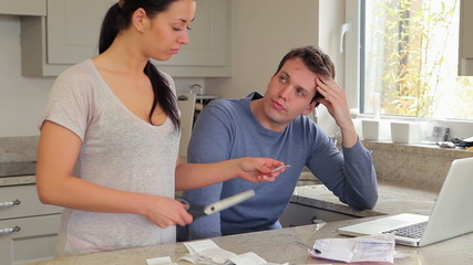 Couple stressing over finances with woman cutting credit card