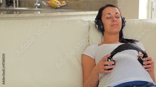 Woman listening to music with headphones on belly