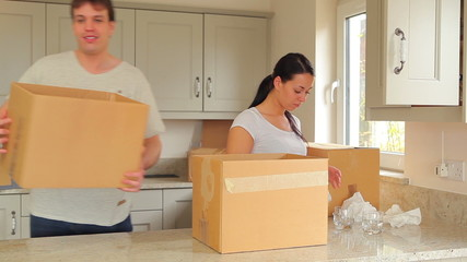 Woman packing up boxes and man moving them