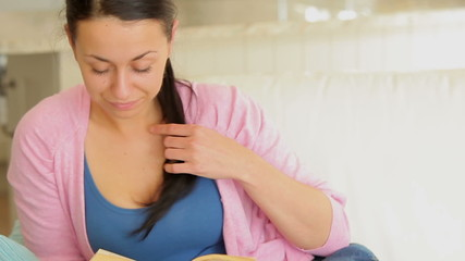 Woman throwing her hair back while reading