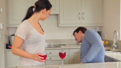 Couple drinking red wine with husband presenting gift