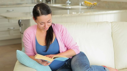 Woman sitting on the couch and reading a book