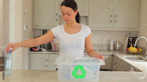 Woman putting plastic into recycling bin