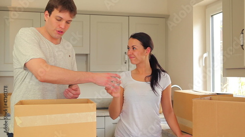 Couple unpacking glasses