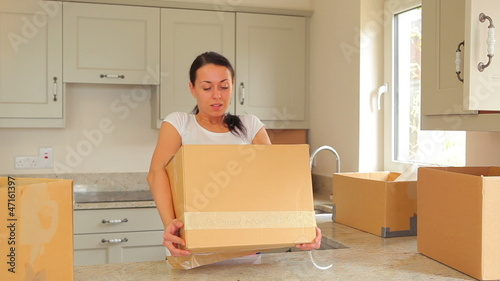 Woman bringing moving boxes into kitchen