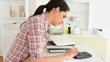 Woman studying with calculator