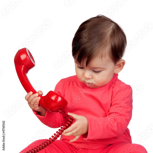 Adorable baby girl with a red phone