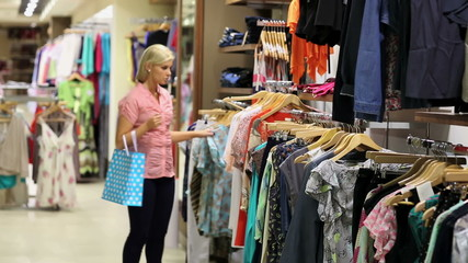 Woman looking at clothes on rail
