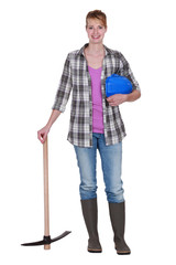 Woman construction worker standing with a pickaxe