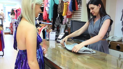 Woman buying clothes at till