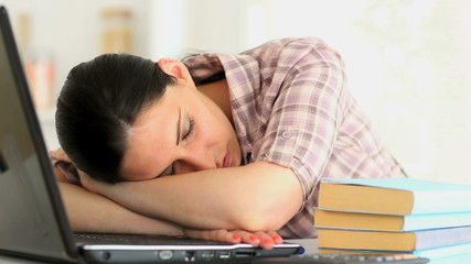 Woman sleeping in front of a laptop