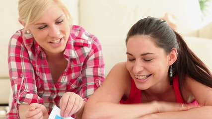 Women looking through magazine and smiling