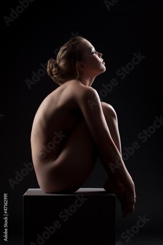 Beautiful nude woman sit in dark on cube - 47162991