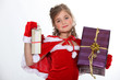 Little girl dressed in festive outfit carrying presents