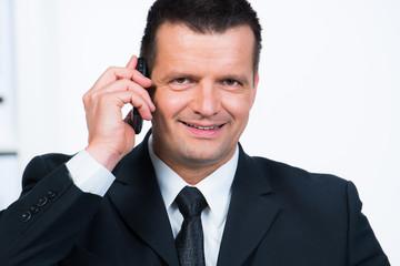manager telefoniert mit dem handy und lächelt