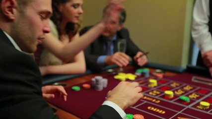 People placing bets at craps table in casino