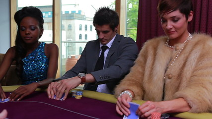 People being dealt poker cards with two people placing bet