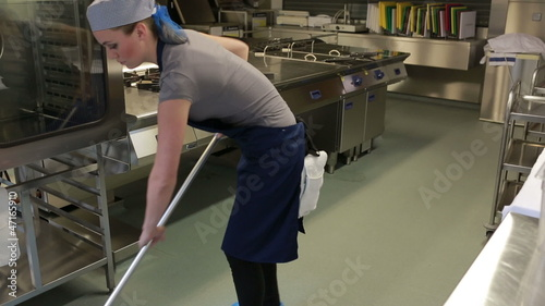 Cleaner of a kitchen wiping the floor