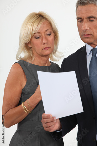 Smart man and woman reading a document