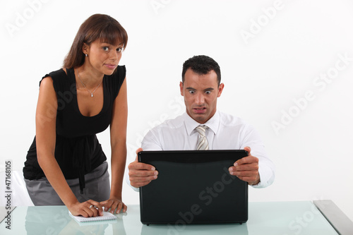 businessman in front of his laptop looking surprised