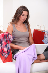Woman sitting with computers and bags full of clothes