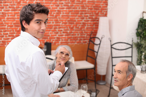 mature couple at restaurant with waiter