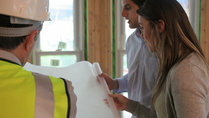 Architect showing blueprints to couple