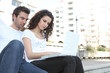 Couple using laptop computer outdoors