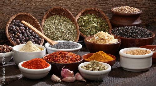 Various bowls of spices over wooden background.