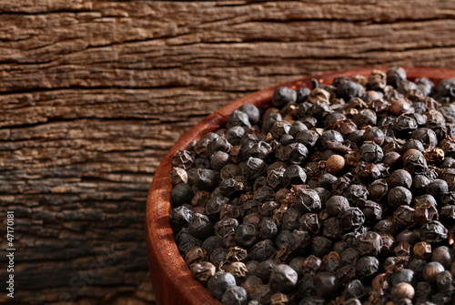 Bowl with black pepper over a wooden background