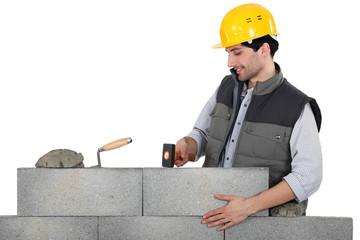 Mason mounting a brick wall