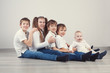Group of kids in jeans sitting on floor
