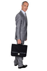 Full length portrait of an older businessman with a briefcase